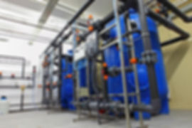 Swimming pool filtration system at basement bright room blue filters pipework