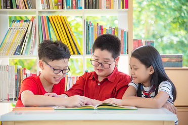 Three asian student reading book togethe