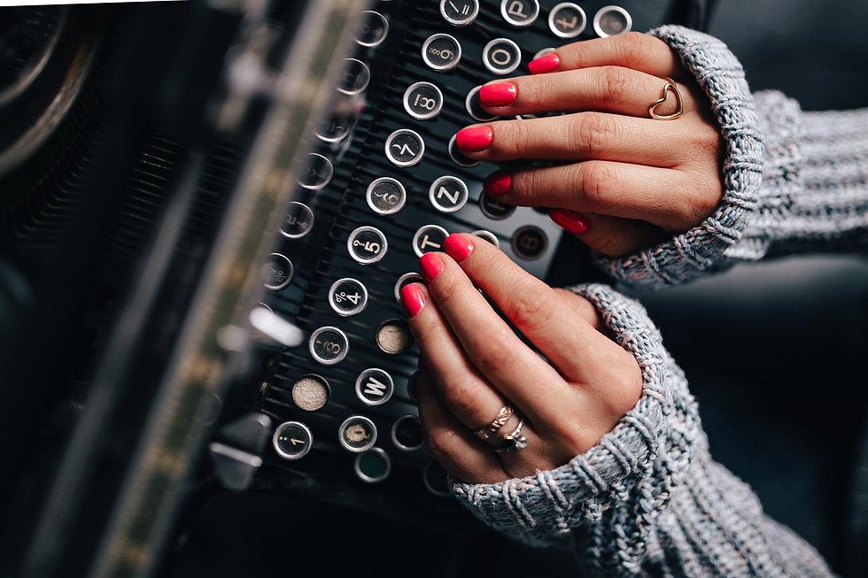 kaboompics_Woman typing on an old typewriter.jpg