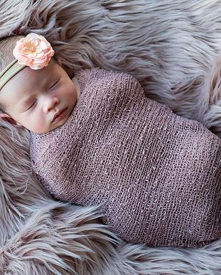 Newborn baby girl in wrap, studio photo