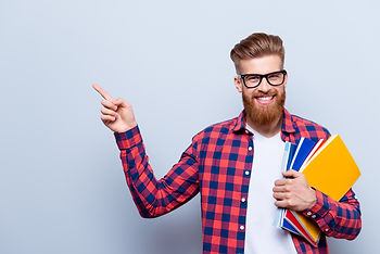 Smiling young nerdy red bearded stylish student is standing with books on pure background