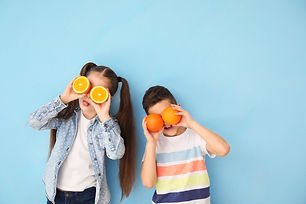 Funny little children with citrus fruit