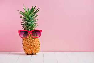 Funny pineapple in a sunglasses on table
