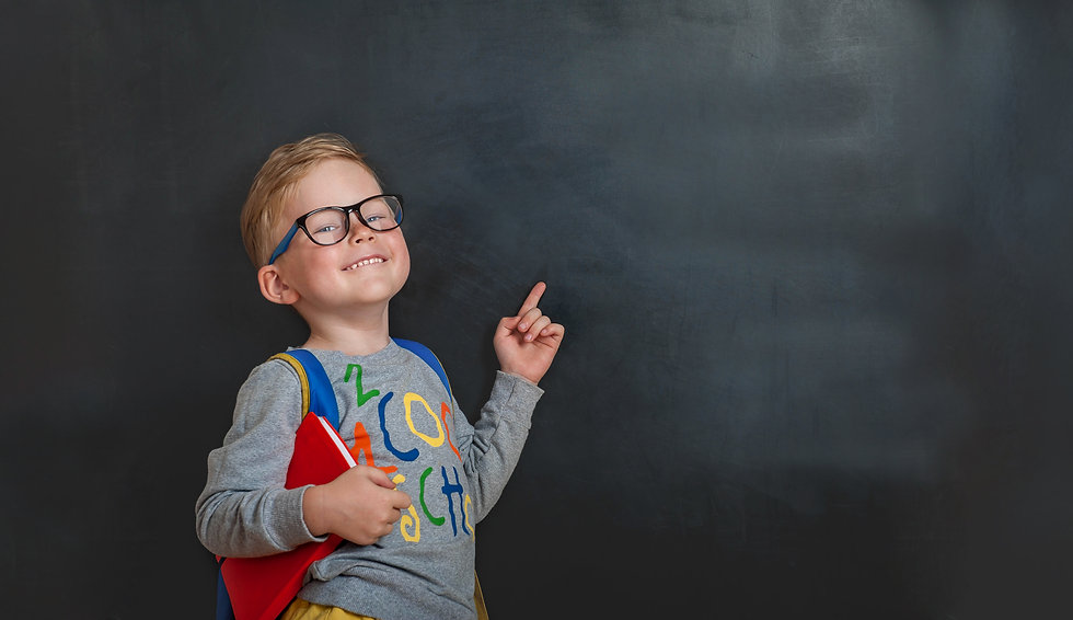 Back to school. Funny little boy in glasses pointing up on blackboard. Child from elementa