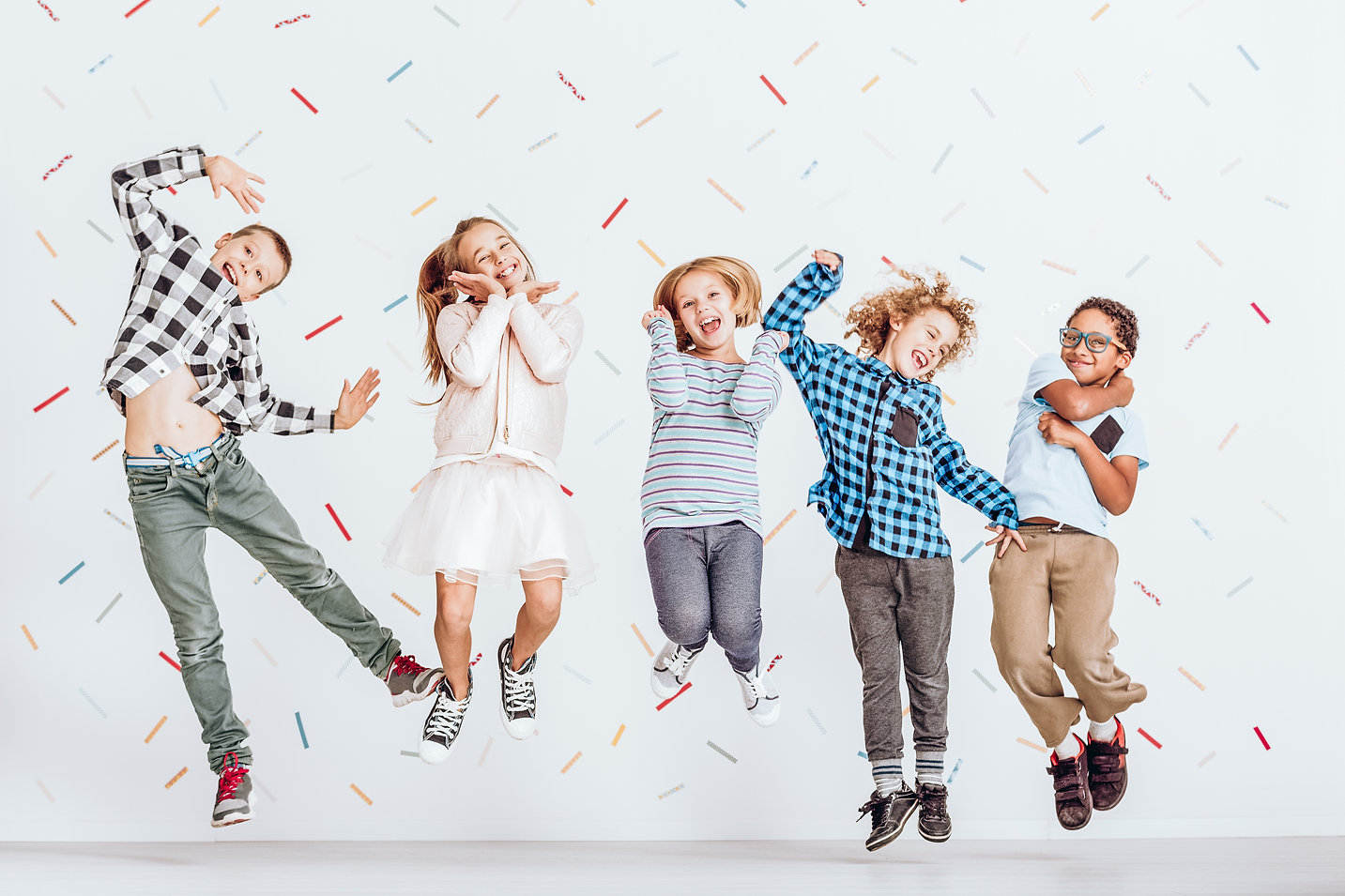 Happy group of kids jumping in a room wi