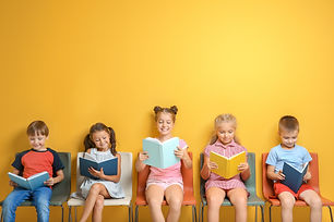 Cute little children reading books while