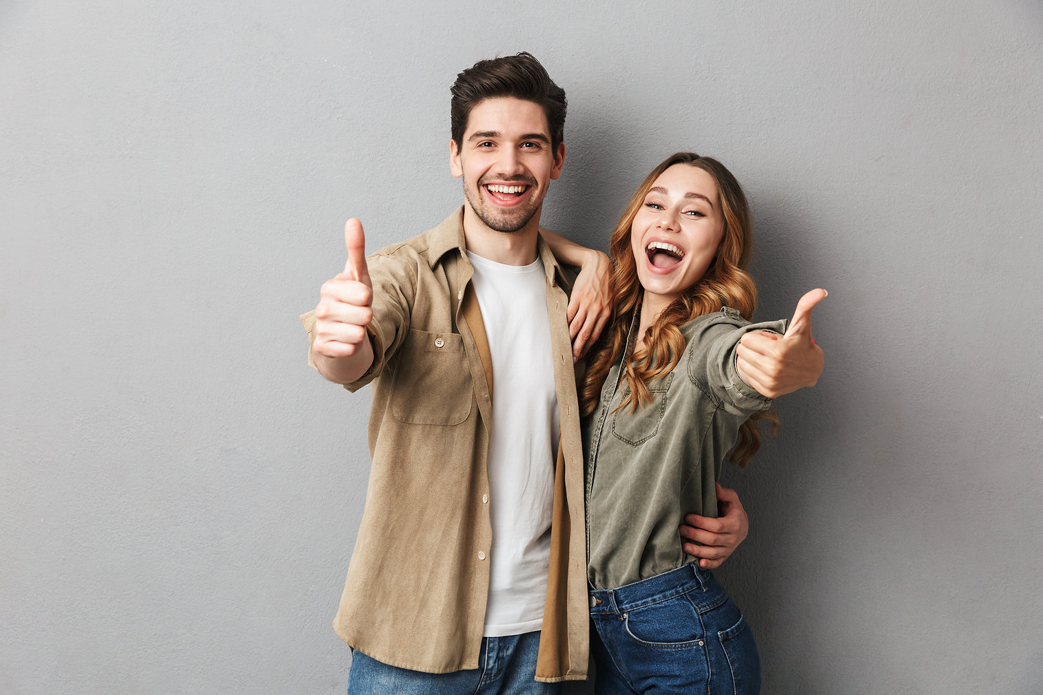 Happy young couple showing thumbs up and