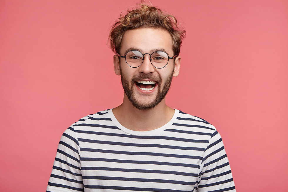 Cheerful hipster guy smiles happily, has