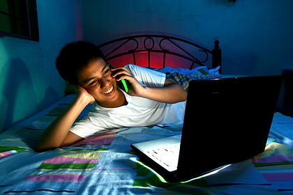 Young Teen in front of a laptop computer and on a bed and using a cellphone or smartphone