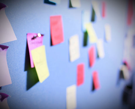 Sticky notes overlapping on a wall represent a brainstorming process.