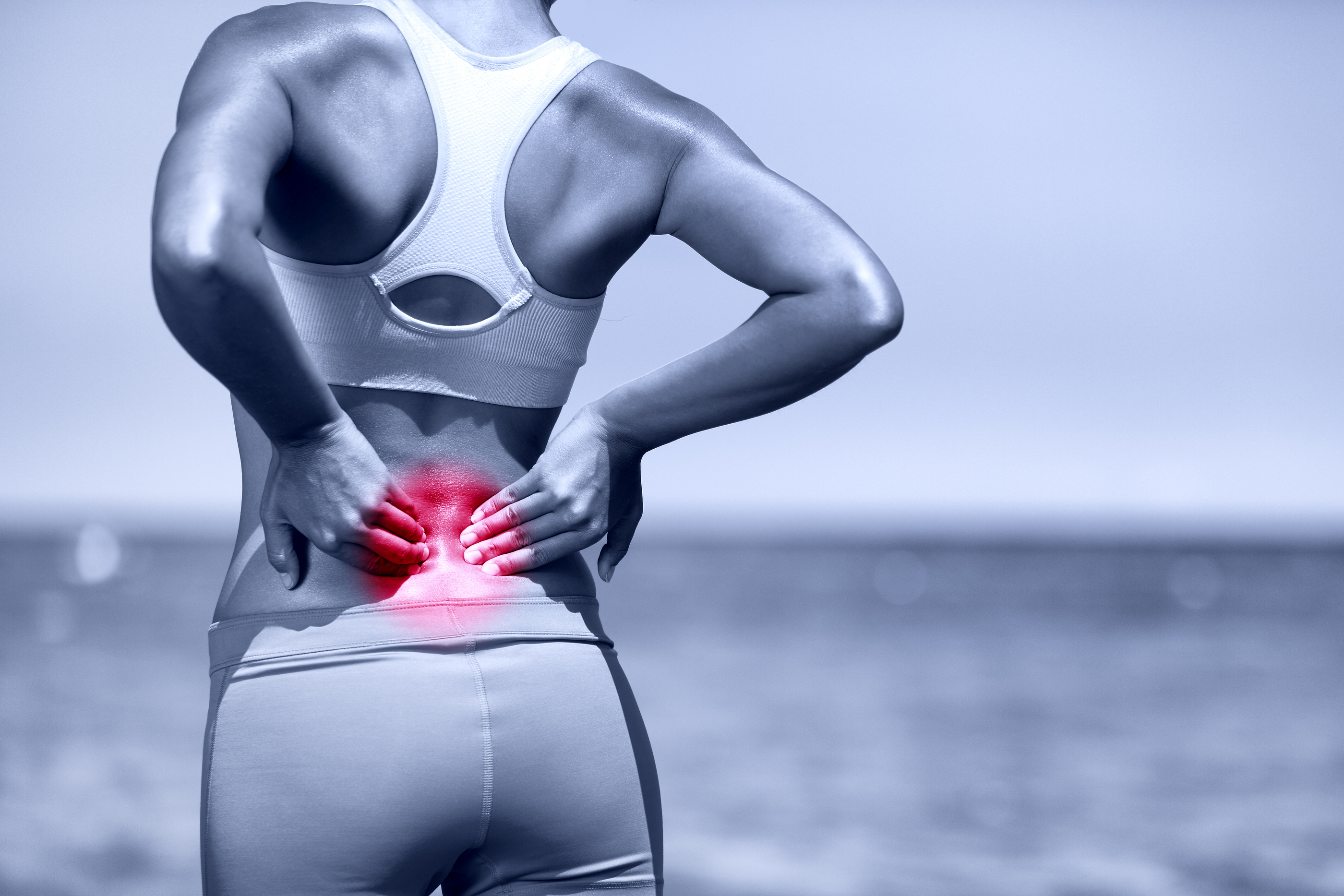 Back pain. Athletic running woman with back injury in sportswear rubbing touching lower back muscles