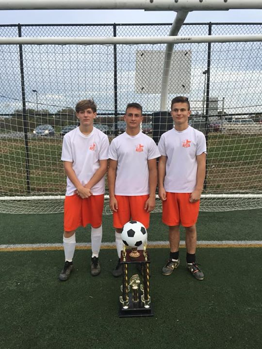 teenage boys with soccer trophy