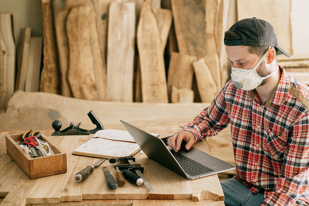 man working in woodshop on laptop Evie Studios