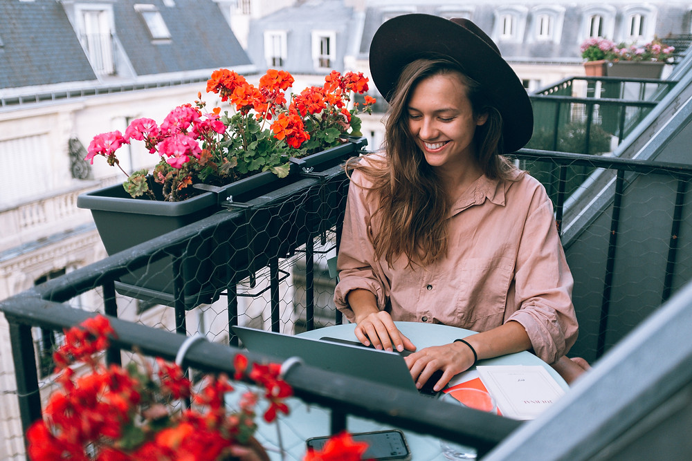 freelance woman in hat sitting on flower balcony and working Evie Studios