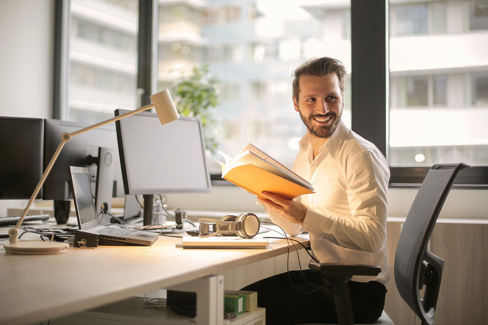 Man sitted at corporate desk and smiling Evie Studios