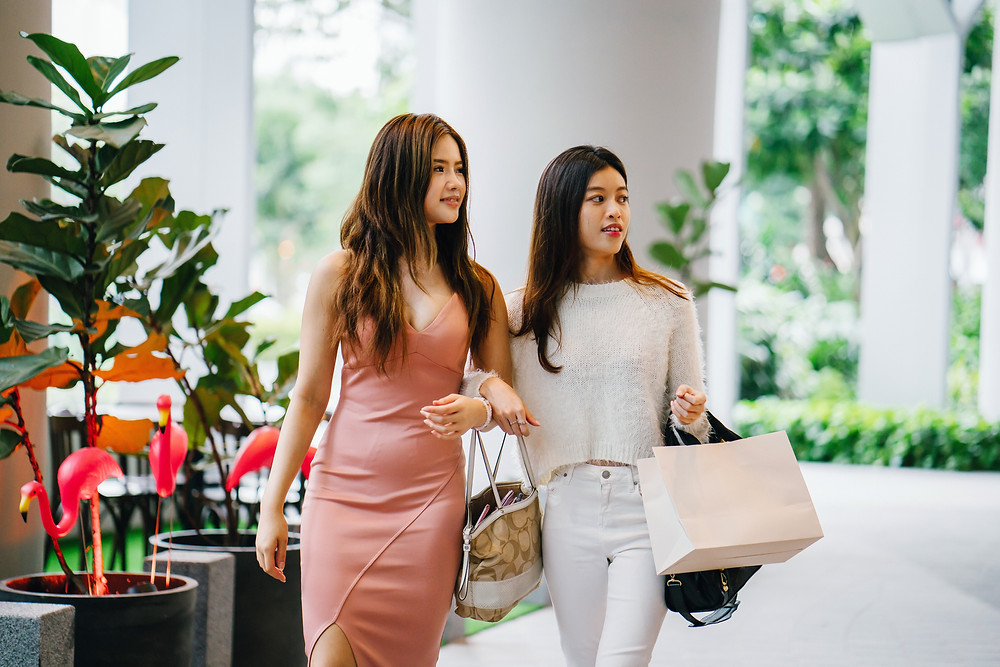 Evie Studios two young women are shopping together with bags in nice mall