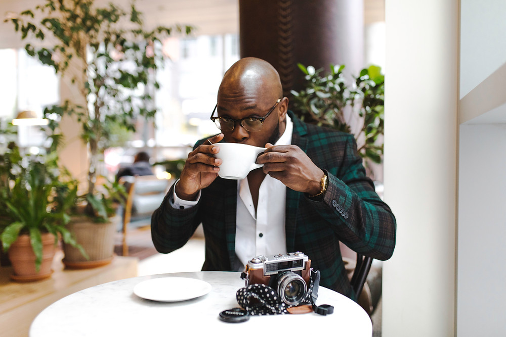 evie studios man drinking coffee at cafe with camera on table