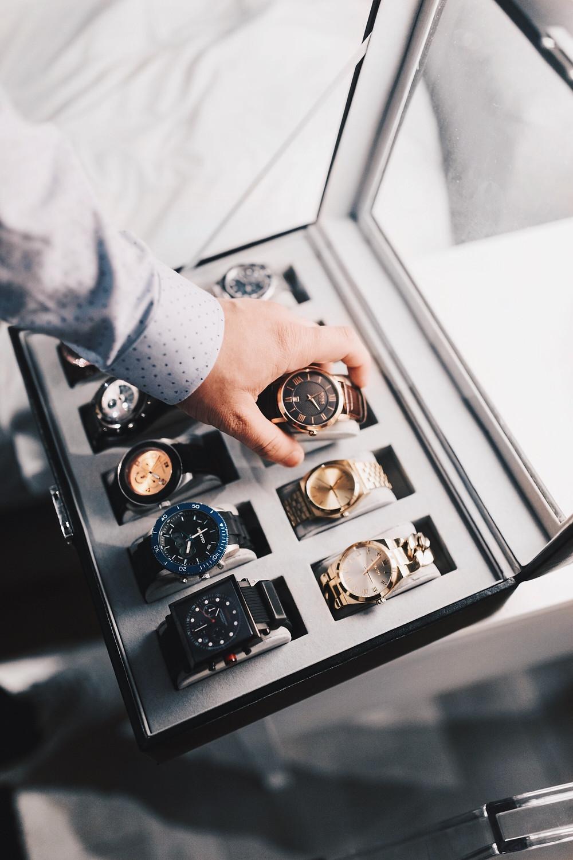Evie Studios  man reaches into case of luxurious watches