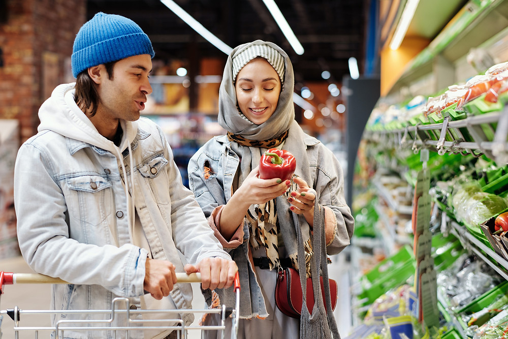 Muslim couple shopping in grocery store Evie Studios