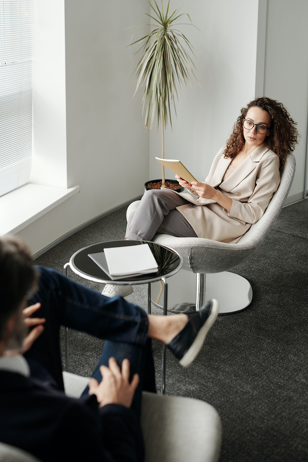 woman sitting in a professional corporate setting discussing with a man Evie Studios