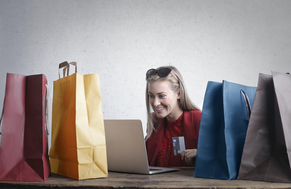 Evie Studios woman online shopping with credit card surrounded by shopping bags