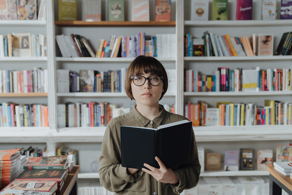evie studios young woman looking at camera with book in study or library