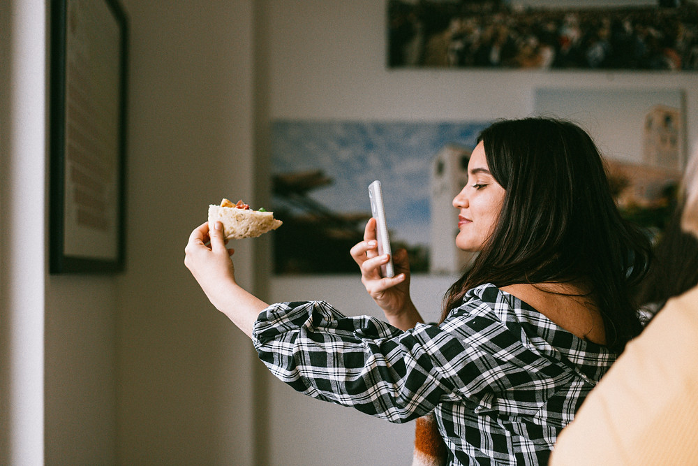 Evie Studios girl in plaid with phone taking picture of pizza