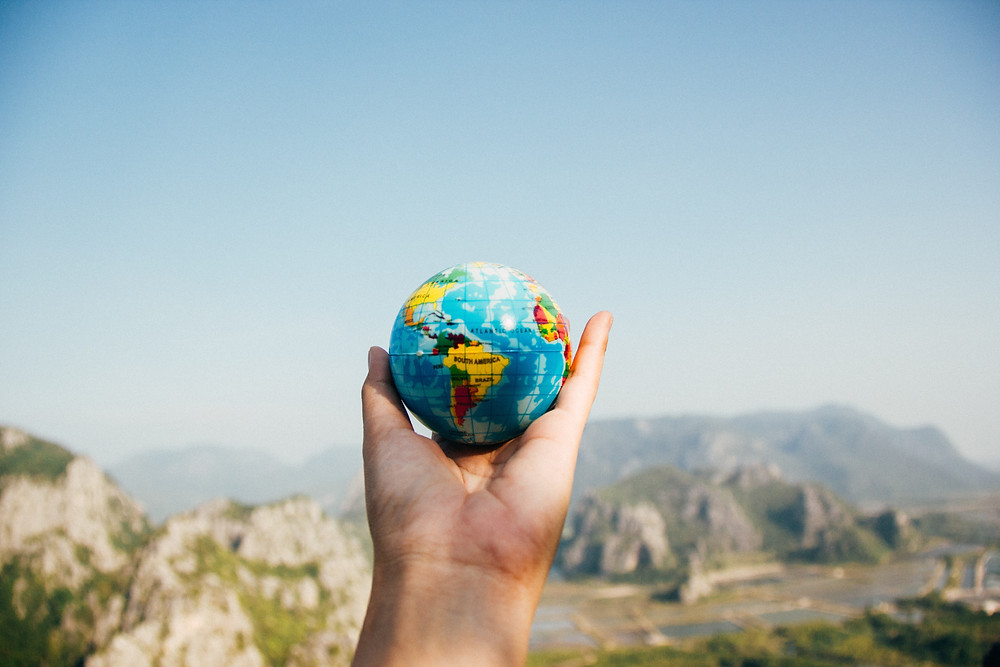 Evie Studios person holding small globe of the world in nice landscape