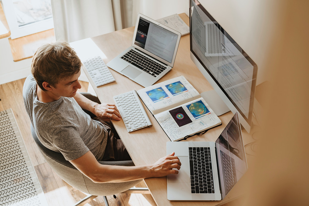 man sitting at desk with two laptops and monitor Evie Studios