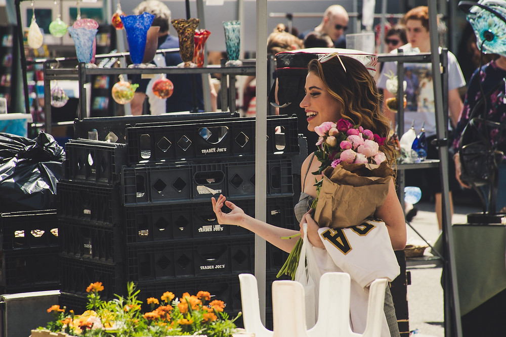 Evie Studios women walks happily out of mall with bouquet of flowers
