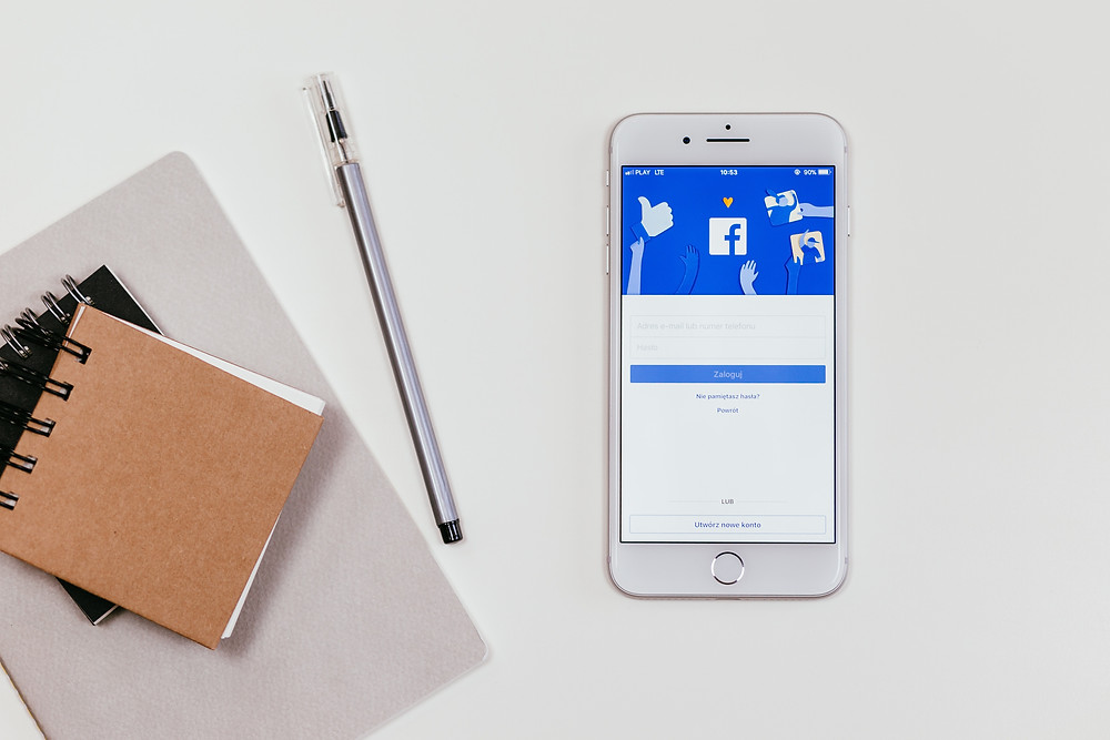 evie studios notepad and iphone with facebook marketing open