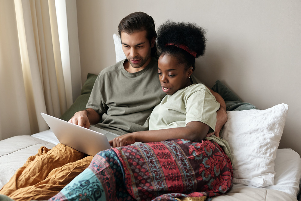 Evie Studios  young couple sits in bed and looks at laptop