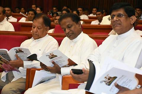Sarath Amunugama sits next to Thilanga Sumathipala to read at a function