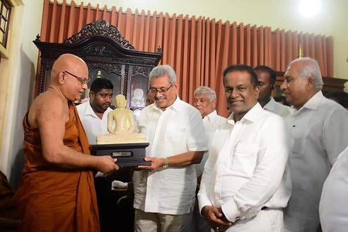 Gotabaya Rajapaksa holds Buddha Statue as Thilanga Sumathipala smiles at us