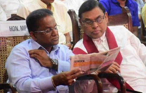 Thilanga Sumathipala reads newspaper with Basil Rajapaksa