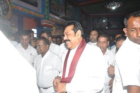 Thilanga Sumathipala and Mahinda Rajapaksa smiling at religious event