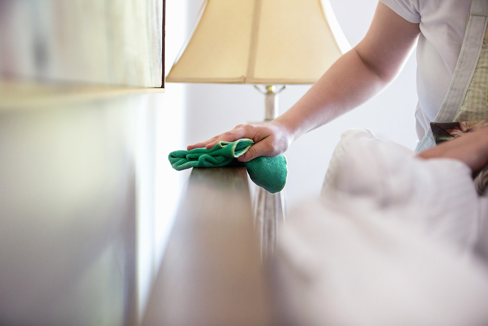 Woman wiping down bed frame using cloth