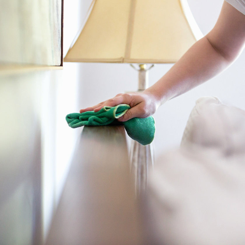 Mother with low grade anxiety cleaning furniture near lamp with rag feeling overwhelmed in St. Louis, MO. Check out maternal mental health counseling st. louis, mo with Marble Wellness. If you're feeling like an overwhelmed mom in missouri we can help you cope with your stressed.