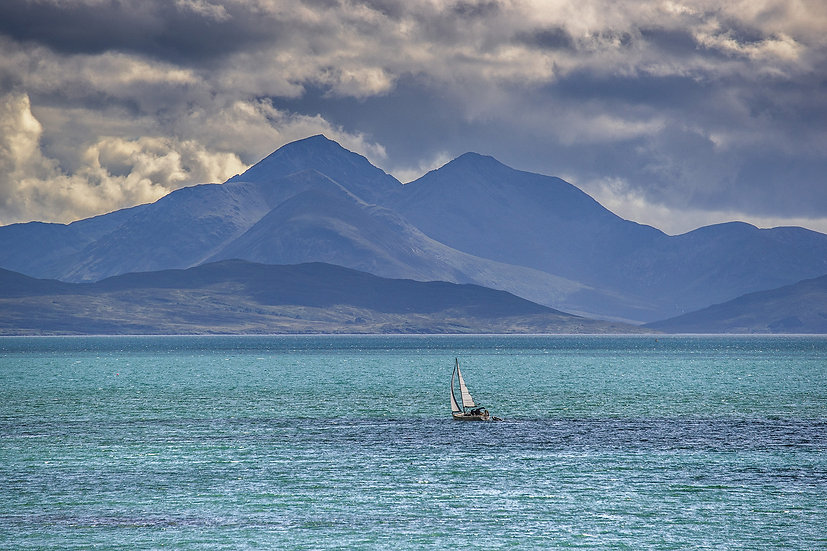 Yacht saling the aqua sea with Skye as a backdrop.