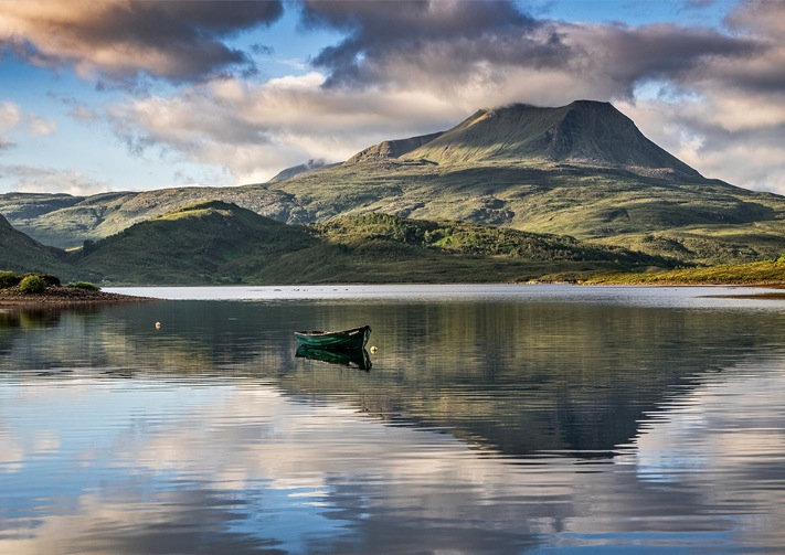 Baosbeheinn and a rowing boat reflecting in Loch Bad an Sgalaig.