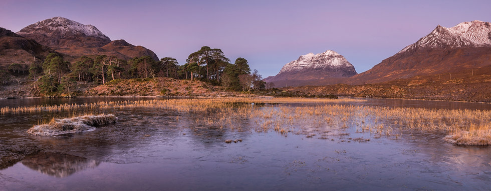 Pink skies before sunrise over a wintry Loch Claire and Liathach