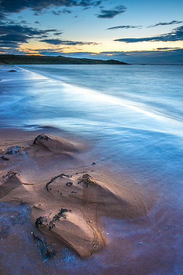 Pearlescent colours on Red Point Beach after sunset after a stormy day.