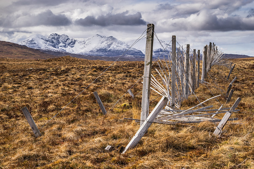 Snow fence showing its age on the Fain, with An Teallach in the background.