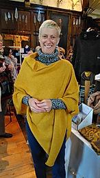 Real customer wearing Torridon poncho in mustard, knitted by Elizabeth Larsen Knitwear.