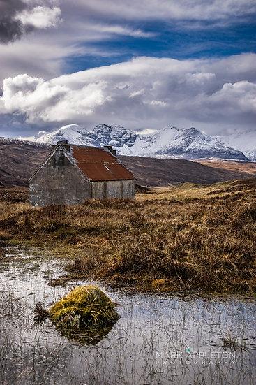 The old Fain Inn looking towards a snow capped An Teallach