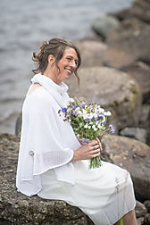 Real bride wearing Seashore poncho and ininity scarf in a hite cotton, knitted by Elizabeth Larsen Knitwear. Knitwear designed and made in Scotland.