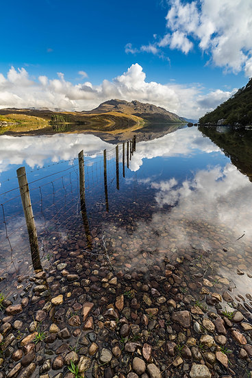 Fence reflecting in a calm Loch Maree with Beinn Airigh Charr in the distance.