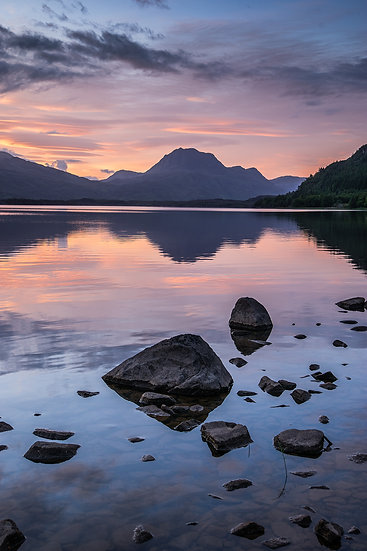 Pastel tones of sunrise reflecting in Loch Maree