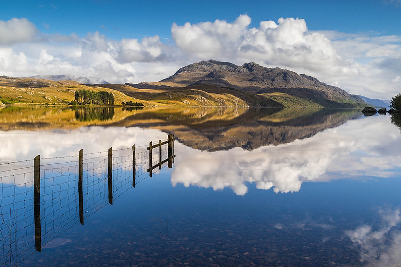 Fence partly submerged in a calm Loch Maree.