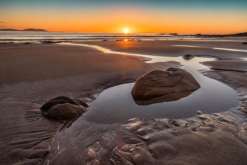 Low tide on Opinan Beach with the sun setting over the Isle of Harris.
